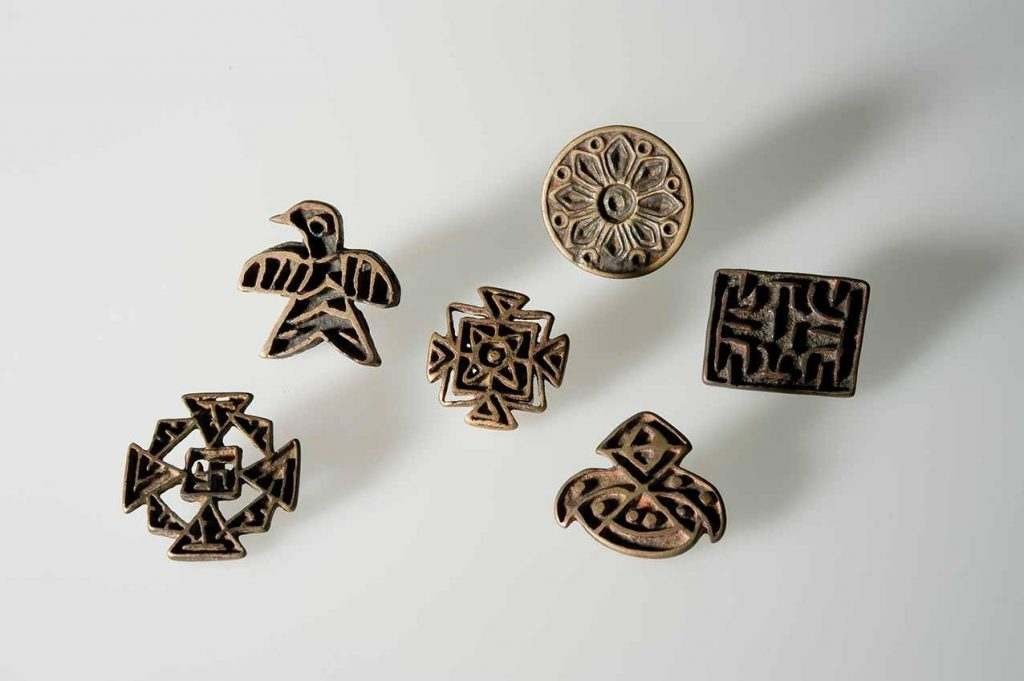 Some examples of the different stylistic categories of Nestorian crosses displayed in the exhibition, including a bird-shaped cross, a Greek cross with a swastika in the centre and a circular cross with a floral motif