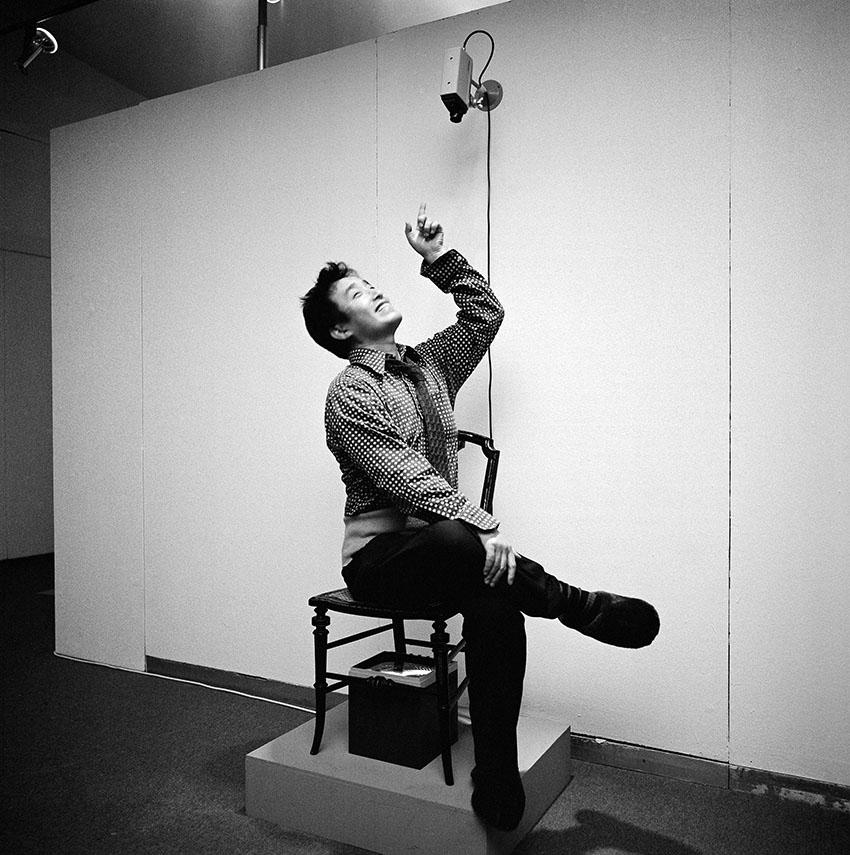 Paik sitting in TV Chair (1968/1976) in Nam June Paik Werke, 1946-1976: Music, Fluxus, Video, 1976 . Photo: © Friedrich Rosenstiel, Cologne