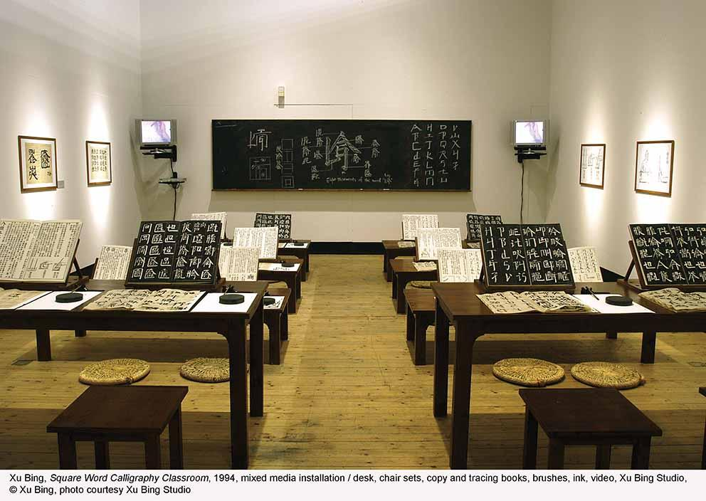 Square Word Calligraphy Classroom (1994), mixed media installation: desk, chair sets, copy and tracing books, brushes, ink, video, Xu Bing Studio © Xu Bing, photo courtesy Xu Bing Studio