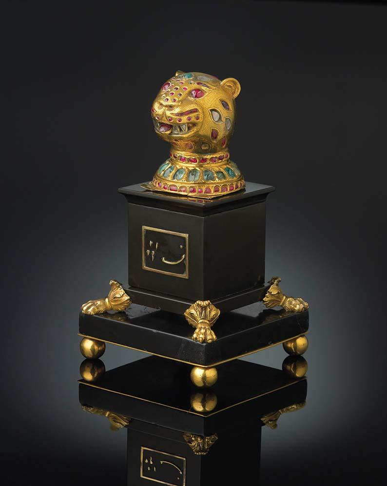 Finial from the throne of Tipu Sultan, Mysore, circa 1790, gold, inlaid with diamonds, rubies, and emeralds. The Al-Thani Collection © Servette Overseas Limited 2013. All rights reserved. Another larger tiger's head from the throne is currently on display in London in the exhibition entitled Gold, at The Queen's Gallery, Buckingham Palace and is part of the Royal Collection.
