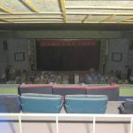 A view inside the cinema, looking from projection room through to the proscenium showing the long-forgotten dust on the leather seats (foreground) and packing case storage are that is currently leased to another party
