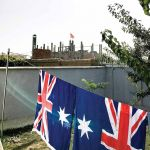 Flags drying in the open outside his Kabul studio with the mosque in the background for The Arrivals #7