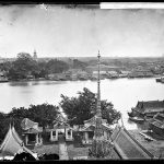 Panorama of the Chao Phraya River and Tarranakosin Island from the prang of Wat Arun, Bangkok 1865. This photograph shows Rattanakosin island and the Chao Phraya River as they were 150 years ago. Traditional wooden and floating houses can be seen lining the river bank, beginning at the Grand Palace and running south as far as Pak Klong Talad. In front of what today is a land-based fruit and vegetable market are a multitude of small boats plying their trade.