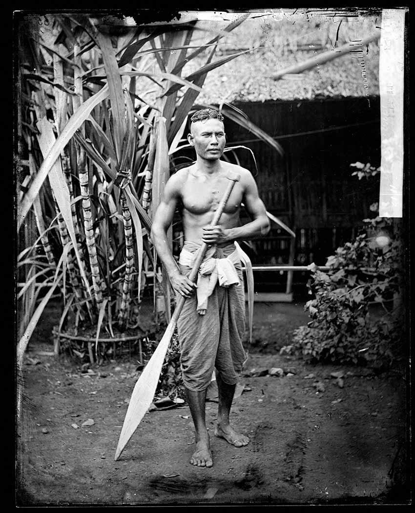 Oarsman, Petchaburi, Thailand 1865. During this period waterborne transport was very popular and many new canals were dug. Settlements grew up along waterways as can been seen in Thomson's panoramas of Bangkok. In particular, where canals entered the main river, markets would develop. The major canals dug by Chinese labourers in this reign were Padung Krung Kasem, Hualampong, Maha Sawat and Pasi Charoen. These were able to take steam boats carrying rice and served as a means of public transport. The boatman strikes a dramatic pose and is dressed in the typical fashion of an ordinary person of the period. He is bare-chested and he wears simple cotton jonggraben and a pakaoma cotton belt.