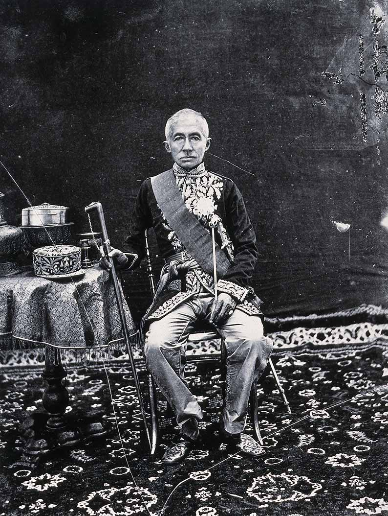 H.M. King Mongkut, King Rama IV, Bangkok, 1865. Portrait of the King taken outside the Aphinao Niwet Throne Hall within the Grand Palace on Monday, 6th October 1865. His Majesty is shown in a full frontal pose in the uniform of a French Field Marshall and wearing the sash of the Legion d'Honneur and star First Class, a decoration presented to him on behalf of Emperor Napoleon III by Admiral Bonard, Commander of the Fleet in Indochina, in the Ananta Samakom Throne Hall on 10th May 1863. On the table are various items of regalia in gold and enamel, namely an oval box adorned with gemstones upon a pedestal tray, a gold ewer on a pedestal tray, a spittoon and a woolen cap embroidered with gold thread in the French style. There is also a small telescope, perhaps in reference to the King's interest in Western science and astronomy.