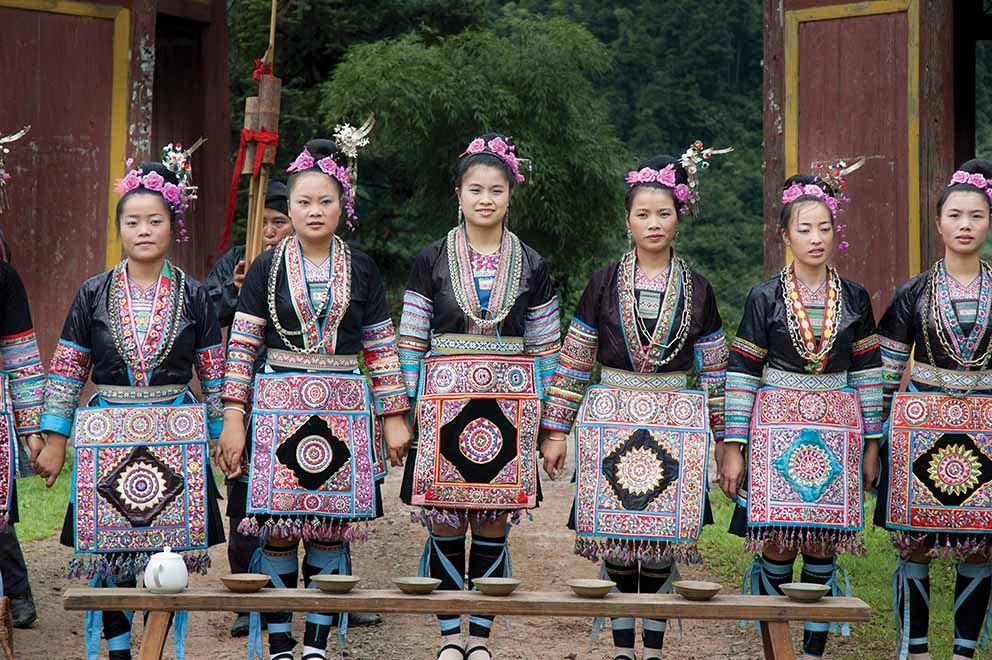 Young women gather at the gate to welcome visitors to Dimen village