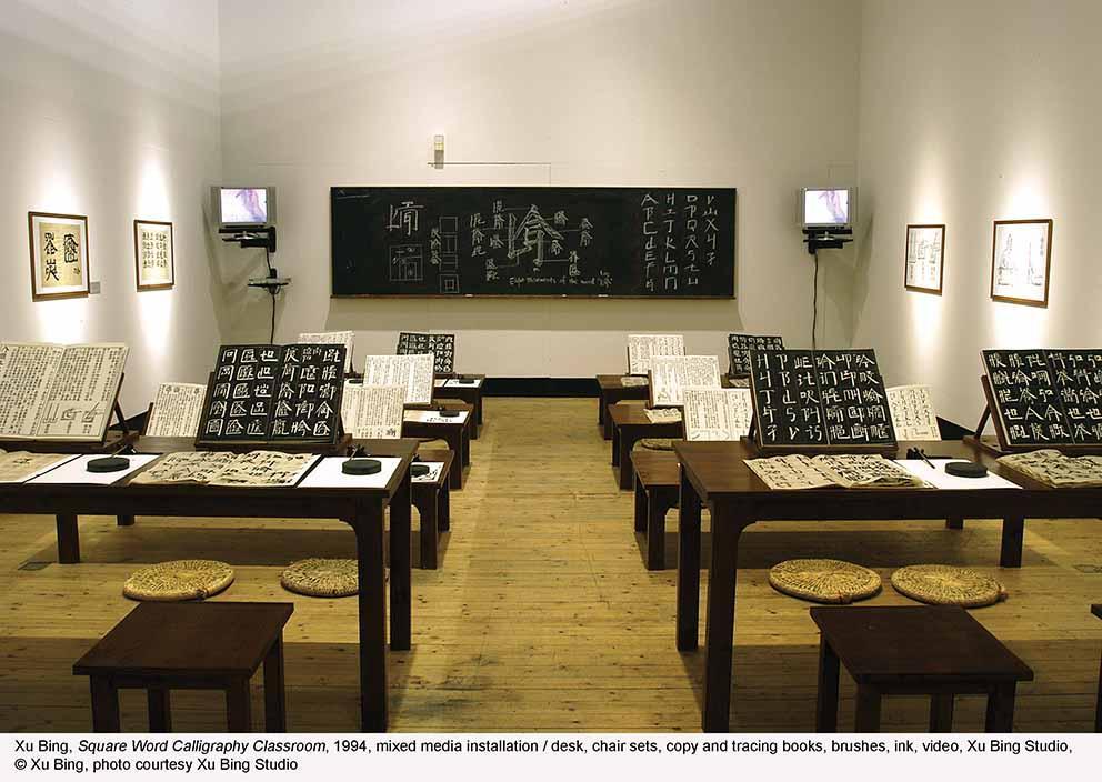 Square Word Calligraphy Classroom (1994), mixed media installation: desk, chair sets, copy and tracing books, brushes, ink, video, Xu Bing Studio © Xu Bing, photo courtesy Xu Bing Studio